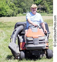 Senior man mowing grass on riding lawnmower