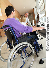 Man in wheelchair working in the office