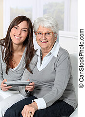 Young woman playing video game with grandmother