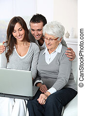 Elderly woman with grandchildren looking at laptop computer