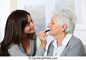 Young woman helping old woman to put makeup on