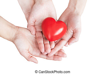 two pairs of hands carefully holding red heart