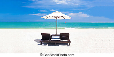 panoramic view of umbrella and two chairs on a tropical beach