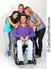 Young man in wheelchair with group of girl friends