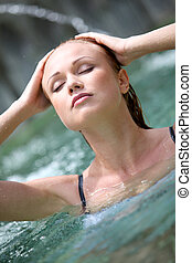 Beautiful woman in spa pool with jets