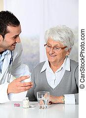 Doctor explaining drugs prescription to elderly woman