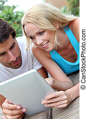 Couple laying on deck chair with electronic tablet