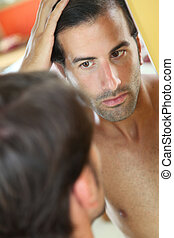 Man with hair concern looking at the mirror