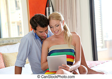 Couple using electronic tablet in hotel room