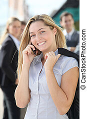 Closeup of blond businesswoman standing outside