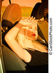 Sexy blonde girl sleeping in the car. Sunset time