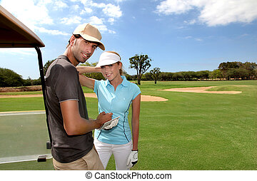 Couple on golf course with cart