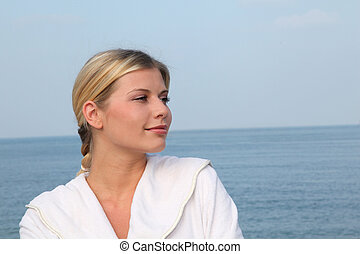 Smiling beautiful woman standing by the sea in bathrobe