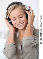 Closeup of blond young girl listening to music