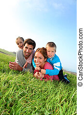 Portrait of happy family laying in country field