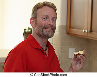 Man Holding an Apple Slice
