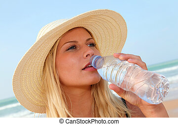 Closeup of woman drinking water at the beach