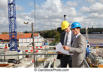 Entrepreneur with architect looking at plan on construction...