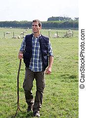 Shepherd standing in pasture land