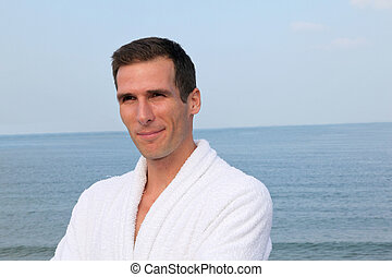 Smiling man standing by the sea in bathrobe