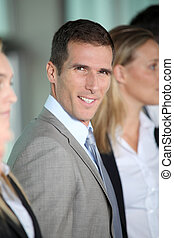 Smiling businessman in front of group