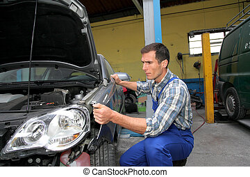 Repairer working on vehicle in garage