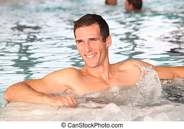 Man bathing in jacuzzi of spa center