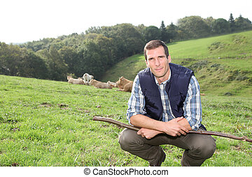 Breeder standing in pasture land