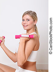 Beautiful blond woman lifting dumbbells in fitness gym