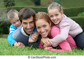 Portrait of happy family lying down in grass