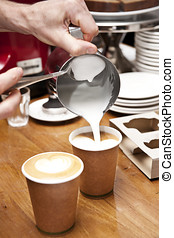 barista pouring milk - a barista pours milk to complete the...