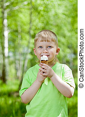 young boy eating a tasty ice cream outdoors