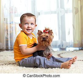 kid hugging puppy indoor