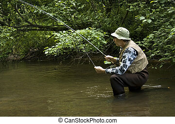 fisherman in waders - fisherman on one knee wearing chest...