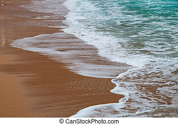 Waves rolling to the sandy beach