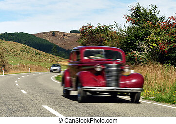 Ford Coupe Vintage Car - Old red Ford car travels on a road...