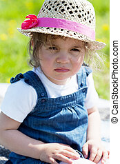 Portrait of the little girl in a straw hat