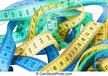 Yellow, green and dark blue measuring tapes on a white background