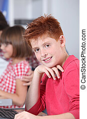 Young red-haired boy in classroom