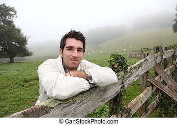 Portrait of breeder leaning on fence