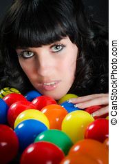 Portrait of attractive woman among colorful balls