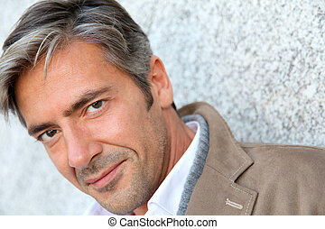 Portrait of handsome mature man in town