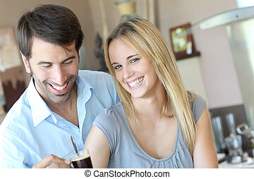 Happy young couple standing in home kitchen