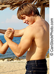 Strong young man showing power on beach