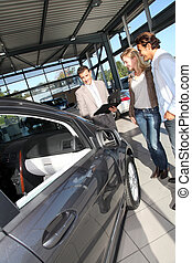 Car seller with couple in showroom