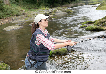 woman with fly fishing rod in river