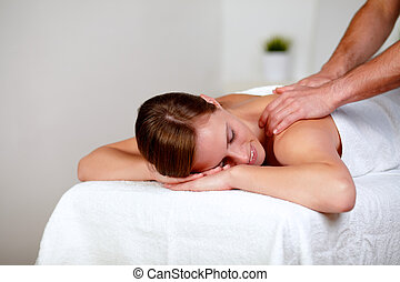 Young woman with eyes closed receiving a massage - Portrait...