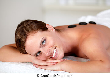 Young woman smiling and relaxing at spa