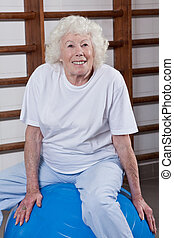 Senior Woman Sits on a Fitball - Happy Senior woman sits on...