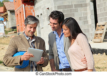 Entrepreneur showing house under construction to couple